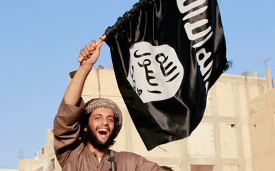 Illustrative: An Islamic State terrorist waves the jihadist organization's flag (CC BY-SA Alatele fr, Flickr)