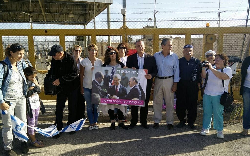 MK Hilik Bar (4th right) attends an anti-war protest at the Quneitra Crossing on the Syrian border, October 18, 2016.  Bar is holding a poster of Sadat, Carter and Begin clasping hands at the White House signing of a 1979 Israel-Egypt peace treaty.