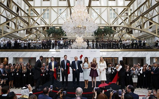 Republican nominee Donald Trump, accompanied by members of his family, holds up a ribbon during the grand opening ceremony of the Trump International Hotel- Old Post Office (Evan Vucci/AP)