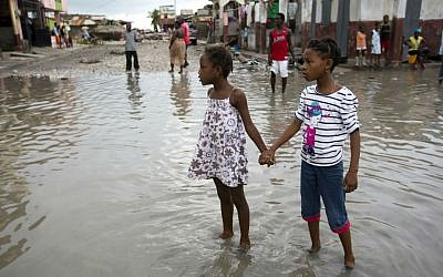 Girls hold hands as they help each other wade through a flooded street after the passing of Hurricane Matthew in Les Cayes, Haiti, Thursday, October 6, 2016. (AP Photo/Dieu Nalio Chery)