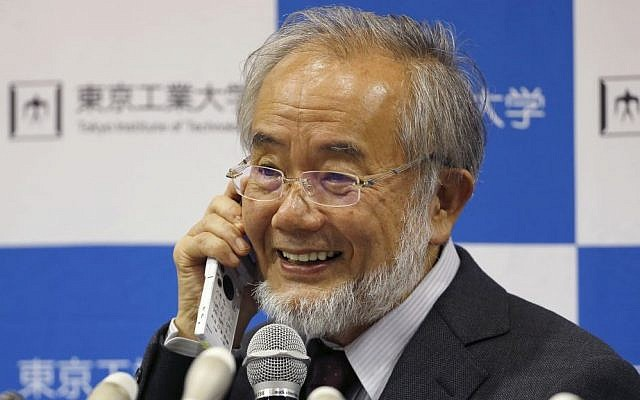 Nobel Prize winner Yoshinori Ohsumi smiles as he speaks with Japanese Prime Minister Shinzo Abe on a mobile phone during a press conference at the Tokyo Institute of Technology in Tokyo Monday, Oct. 3, 2016. (Shizuo Kambayashi/AP)