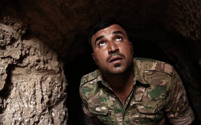 A peshmerga fighter looks out of the entrance of an underground tunnel built by Islamic State fighters, Tuesday, Oct. 18, 2016.  (AP/Bram Janssen)