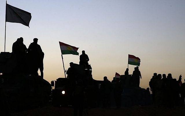 Kurdish Peshmerga fighters stand on top of a military vehicle as they advance towards villages in Khazer, about 19 miles east of Mosul, Iraq, Monday, Oct. 17, 2016 (AP Photo/Bram Janssen)