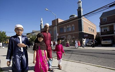 Muslim children walk with their father past a mosque after the completion of a service for the Eid al-Adha holiday on Sept. 12, 2016, in the Queens borough of New York. (AP Photo/Mark Lennihan)