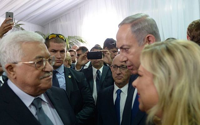 Prime Minister Benjamin Netanyahu and his wife Sara meet with Palestinian Authority President Mahmoud Abbas during the state funeral of late Israeli president Shimon Peres, at Mount Herzl in Jerusalem, September 30, 2016. (Amos Ben Gershom/GPO)