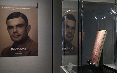 FILE - In this Thursday, March 19, 2015 file photo, a notebook of British mathematician and pioneer in computer science Alan Turing, the World War II code-breaking genius, is displayed in front of his portrait during an auction preview in Hong Kong. (Kin Cheung/AP)