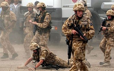 In this May 6, 2006 file photo, a British trooper falls after apparently being hit by a rock, as British troops move towards a helicopter crash site in Basra, Iraq's second-largest city, 550 kilometers (340 miles) southeast of Baghdad. Britain's prime minister announced plans on Oct. 4, 2016 to protect British troops from dubious legal claims made during conflicts. (AP Photo/Nabil Al-Jurani, File)