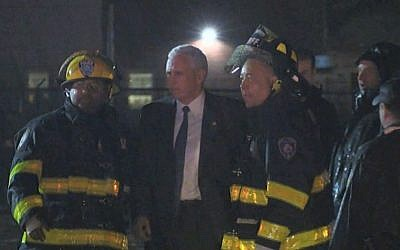 Republican vice presidential candidate Indiana Gov. Mike Pence talks with firefighters at New York's LaGuardia Airport after his campaign plane slide off the runway while landing on Thursday, Oct. 27, 2016. (TV Network Pool via AP)