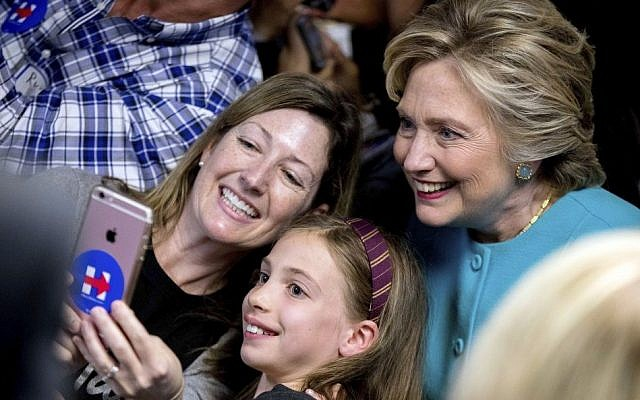 Democratic presidential candidate Hillary Clinton takes a photograph with supporters at a campaign office in Seattle, Friday, October 14, 2016. (AP Photo/Andrew Harnik)