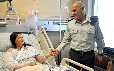 Cpt. Or Ben-Yehuda shakes hands with former head of the IDF's Southern Command Maj. Gen. Sami Turgeman while she was recuperating from wounds sustained in an attack by smugglers in October 2014. (IDF Spokesperson's Unit)