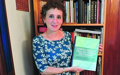 Gitl Schaechter-Viswanath holding her 'Comprehensive English-Yiddish Dictionary.' (The Jewish Standard)