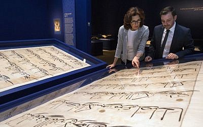 "In this photo taken Oct. 20, 2016, Massumeh Farhad, left, and Simon Rettig, curators of the exhibit ""The Art of the Qur'an: Treasures from the Museum of Turkish and Islamic Arts,"" look at pages from a 5-foot by 7-foot Quran displayed as part of the exhibit at the Sackler Gallery in Washington. (AP/Molly Riley)"