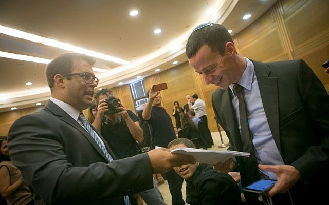 Likud MK Oren Hazan (L) hands Channel 2 News reporter Amit Segal a copy of the libel lawsuit the Knesset member filed against him, October 12, 2015. (Miriam Alster/Flash90)