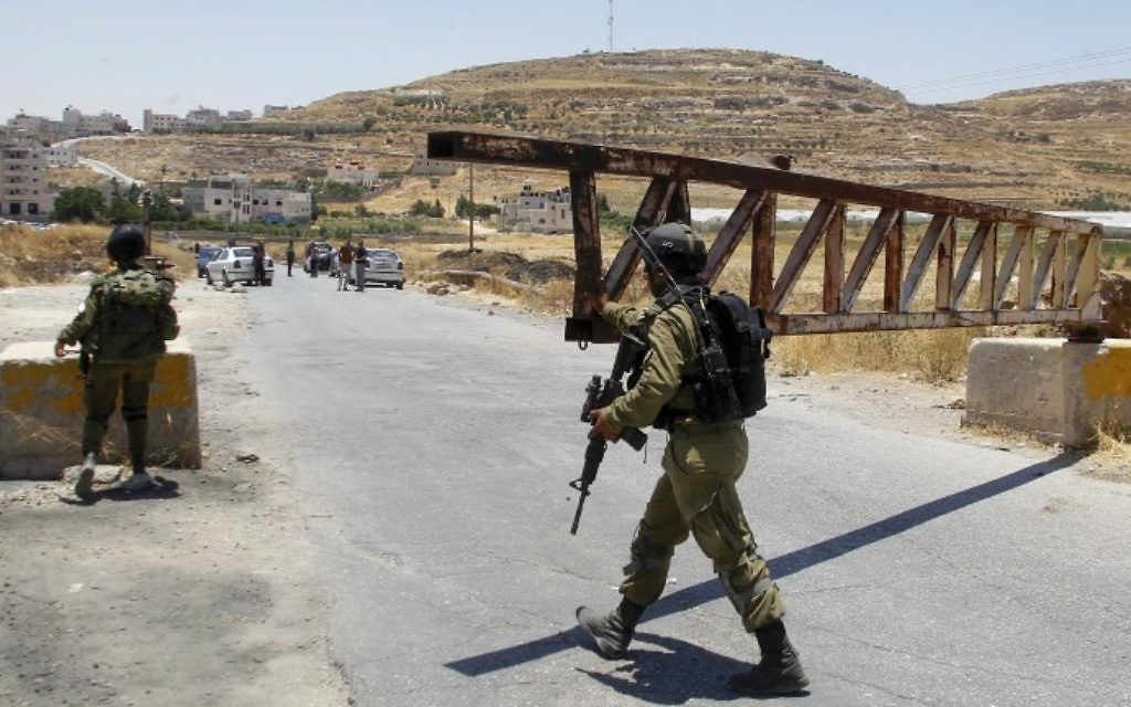 An Israeli soldier closes a gate at a checkpoint in the West Bank village of Yatta, near Hebron, on July 3, 2016. (Wisam Hashlamoun/Flash90)