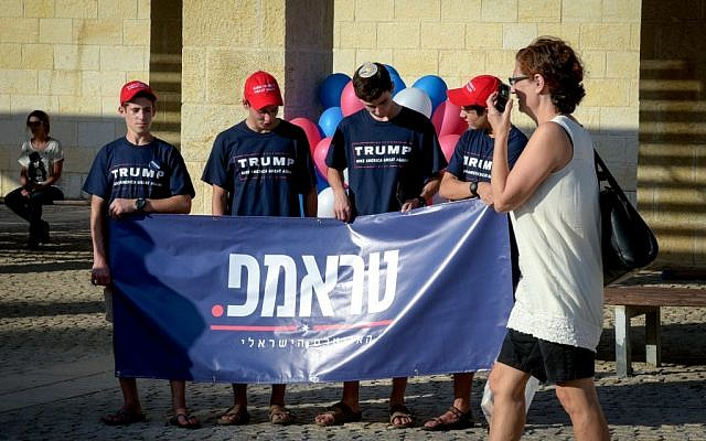 A woman walks by Trump supporters at the opening of the campaign supporting the Republican presidential candidate Donald Trump in Modiin on August 15, 2016. (Joe Davids/Flash90)