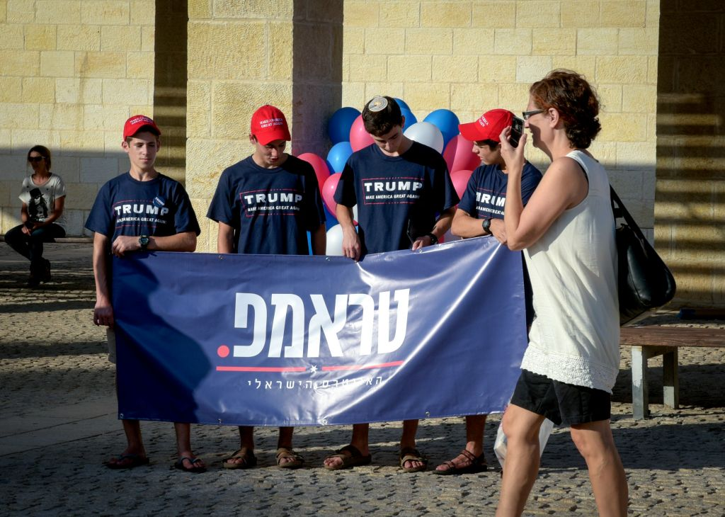 A woman walks by Trump supporters at the opening of the campaign supporting the Republican presidential candidate Donald Trump in Modi'in Israel on August 15, 2016.( Joe Davids/FLASH90)
