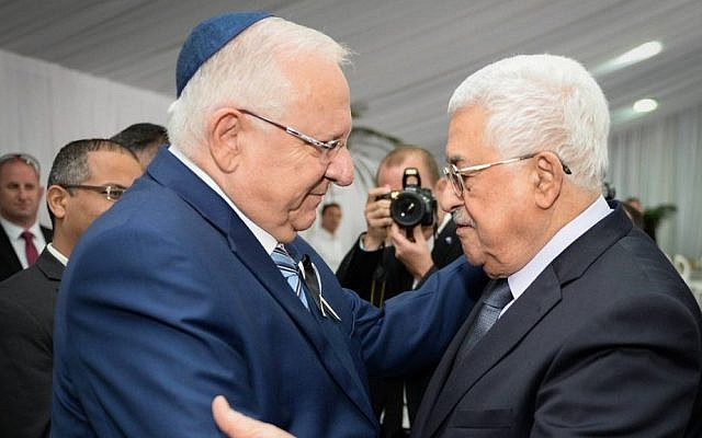 President Reuven Rivlin, right, meets Palestinian Authority President Mahmoud Abbas during the funeral for late former president Shimon Peres at Mount Herzl Cemetery in Jerusalem, on September 30, 2016. (Mark Neyman/GPO)