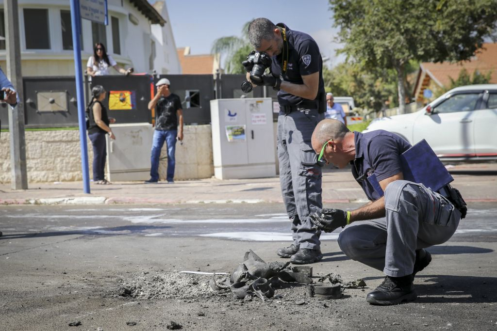Police sappers dig out piece of a rocket launched from the Gaza Strip that struck a road in the southern city of Sderot on October 5, 2016. ( FLASH90)