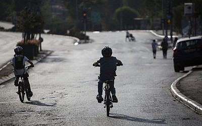 Children  ride bicycles on a road empty of cars in Jerusalem, on Yom Kippur, October 12, 2016 (Hadas Parush/Flash 90)
