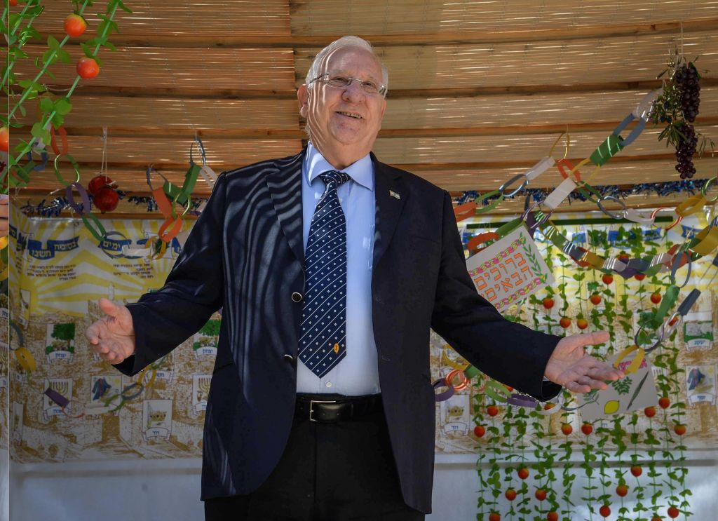 President Reuven Rivlin decorates a Sukka at the President's residence in Jerusalem for the upcoming Jewish holiday of Sukkot, on October 13, 2016. (Mark Neyman/GPO)