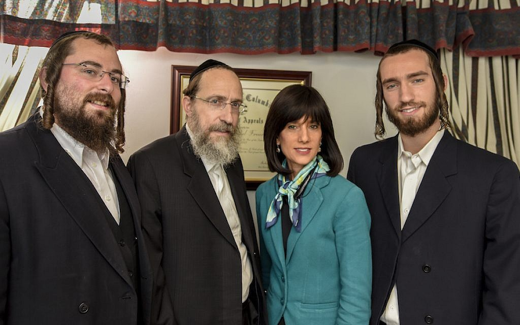 Rachel Freier in her Borough Park law office with, from left to right,  nephew