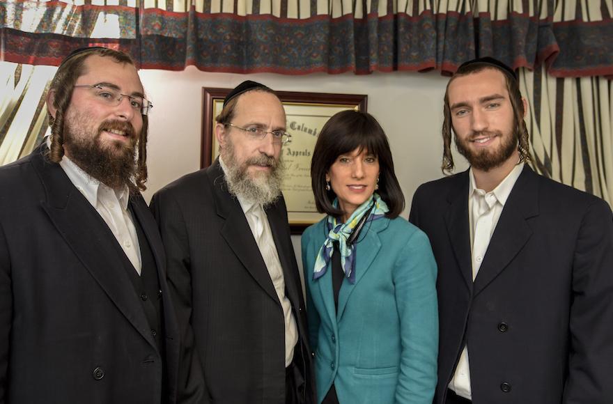 Rachel Freier in her Borough Park law office with, from left to right, nephew Shmuel Freier, husband David Freier and son Mayer Freier. (Andrew Katz/JTA)