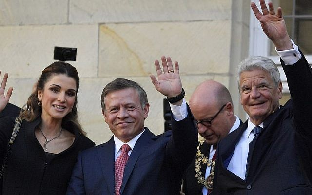 Queen Rania, left, and King Abdullah of Jordan, center, with German President Joachim Gauck wave to citizens on the historic town hall balcony in Muenster, Germany, Saturday, Oct. 8, 2016. (AP Photo/Martin Meissner)