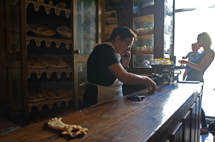 Herminia Rodriguez, left, preparing change for a customer at her Jewish bakery in Ribadavia, September 24, 2016. (Cnaan Liphshiz/JTA)