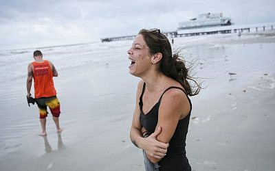 Emily Vulpi, 29, laughs as the winds pick up as she walks along the beach with Ryan Bell, 28, ahead of expected landfall of Hurricane Matthew in Daytona Beach, Florida, on Thursday, Oct. 6, 2016. (Will Vragovic/Tampa Bay Times via AP)