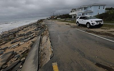 An official vehicle passes along the shoulder of Highway A1A after it was partial washed away by Hurricane Matthew, Friday, Oct. 7, 2016, in Flagler Beach, Florida (AP Photo/Eric Gay)