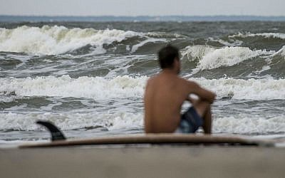 Eric Dunn sits on the northern end of Tybee Island's beach watching larger than average waves roll in as a result of Hurricane Matthew's approach, Tuesday, Oct. 4, 2016 in Tybee Island, Georgia. (Josh Galemore/Savannah Morning News via AP)
