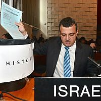 Israel's ambassador to UNESCO Carmel Shama-Hacohen throws a copy of the day's resolution on Jerusalem in the trash, October 26, 2016. (Erez Lichtfeld)