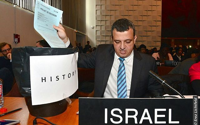 Israel's ambassador to UNESCO Carmel Shama-Hacohen throws a copy of the day's resolution on Jerusalem in the trash on Wednesday, October 26, 2016. (Erez Lichtfeld)