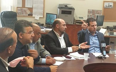 Joint (Arab) List chair Aymen Odeh (right) talking to party MKs at the weekly faction meeting, October 31, 2016. (Raoul Wootliff/Times of Israel)