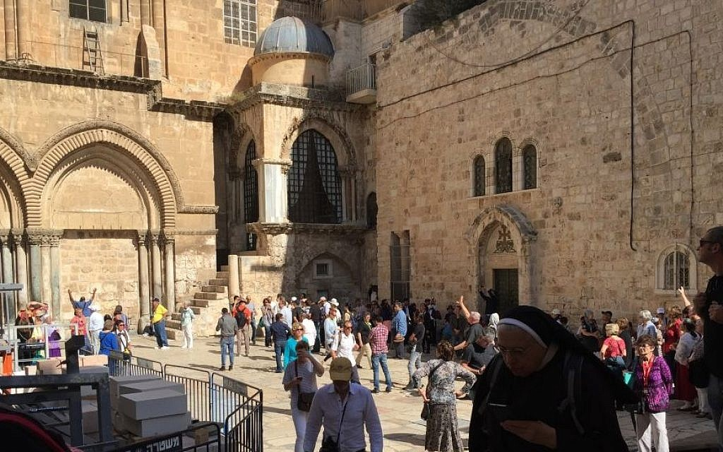 Visitors outside the Church of the Holy Sepulchre in Jerusalem, October 28, 2016. The Immovable Ladder is seen at top left (Times of Israel staff)