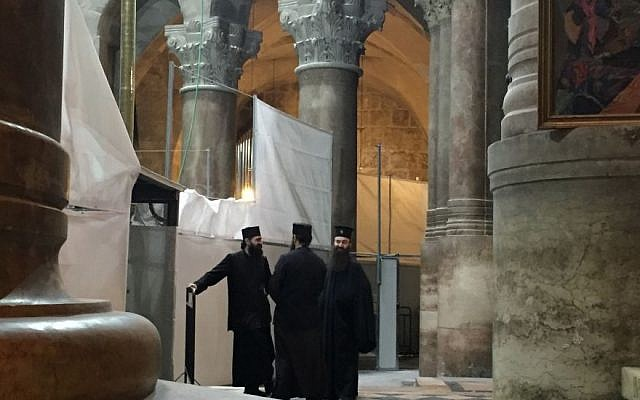 Clergymen outside the Edicule, which houses Jesus's tomb, at the Church of the Holy Sepulchre in Jerusalem, October 28, 2016 (Times of Israel staff)