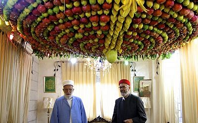 The Samaritan high priest, Abdullah Wassef Tawfiq, stands with his brother Husney Cohen inside his living room with a home-made 'sukkah' made from fresh fruit for the holiday of Tabernacles, or Sukkot, in Mount Gerizim near the West Bank town of Nablus, on October 18, 2016. (Dov Lieber / Times of  Israel)