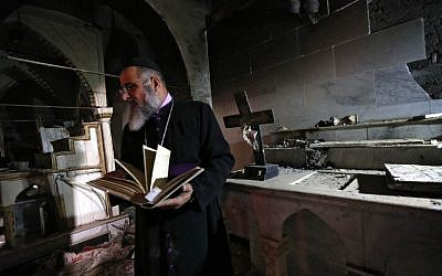 David Dosha, the priest of the Church of Mart Shmony, located in the Christian Iraqi town of Bartalla, about 15 kilometers (10 miles) east of Mosul, inspects the damage on October 24, 2016, at the church's compound after Iraqi forces retook control of the town from jihadists of the Islamic State group. (AFP/Safin Hamed)