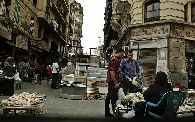 In this Tuesday, Oct. 18, 2016 photo, a woman sells bread near the Tawfiqia market in downtown Cairo, Egypt. (AP Photo/Nariman El-Mofty, File)