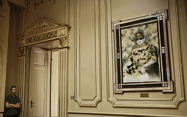 In this Monday, Oct. 10, 2016 file photo, an Egyptian museum worker looks at a portrait of Egyptian President Abdel-Fattah el-Sissi inside the Presidential Gifts Hall in Abdeen Palace, one of downtown Cairo's historic palaces. (AP Photo/Nariman El-Mofty, File)