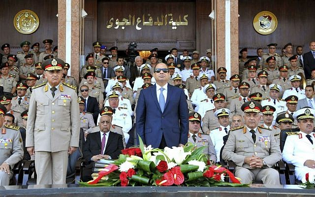 In this July 22, 2015, file photo, provided by the office of the Egyptian Presidency, Egyptian President Abdel-Fattah el-Sissi, center, and Defense Minister Sedqi Sobh, left, stand at attention at the Air Defense Academy in Alexandria, Egypt. (Mohammed Samaha/Egyptian Presidency via AP, File)