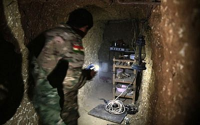 A peshmerga fighter walks through the kitchen of an underground tunnel made by Islamic State fighters, Tuesday, October 18, 2016, near Mosul. (AP/Bram Janssen)