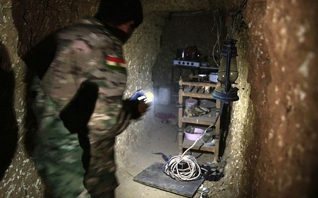 A peshmerga fighter walks through the kitchen of an underground tunnel made by Islamic State fighters, Tuesday, Oct. 18, 2016. (AP/Bram Janssen)