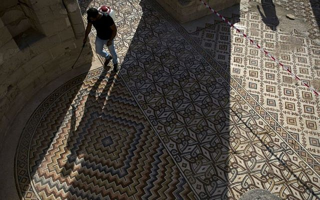 A laborer from the Palestinian Ministry of Tourism and Antiquities works at the site of a 7th century, 827 square meter (8900 square ft) mosaic ahead of the opening ceremony at the Islamic archaeological site of Hisham Palace, in the West Bank city of Jericho, Thursday, Oct. 20, 2016. (AP Photo/Nasser Nasser)