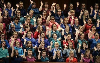 In this April 2, 2016, file photo, members of the combined Choir from BYU-Idaho raise their hands during a sustaining vote at the two-day Mormon church conference in Salt Lake City, Utah. (AP Photo/Rick Bowmer, File)
