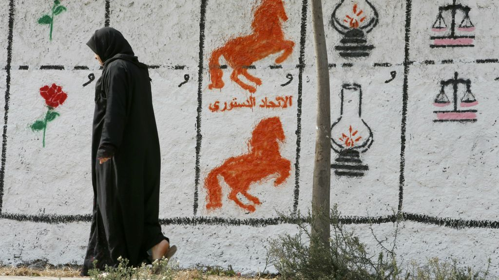 A Moroccan woman walks past electoral paintings representing political  party logos for the upcoming municipal elections