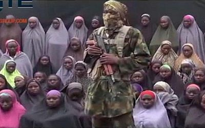 In this undated image taken from video distributed Sunday, Aug. 14, 2016, an alleged Boko Haram soldier stands in front of a group of girls alleged to be some of the 276 abducted Chibok schoolgirls (Militant video/Site Institute via AP)
