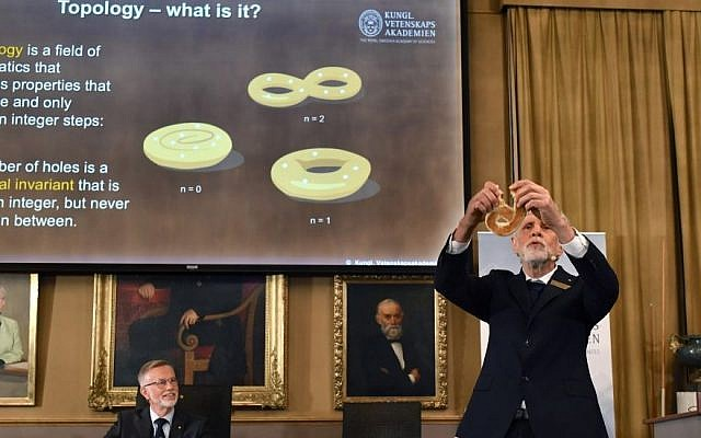 Professor Thors Hans Hansson gives a demonstration using a bagel to explain the work of the winners of the Nobel Prize in physics, at the Royal Swedish Academy of Sciences, in Stockholm, Sweden, Tuesday, Oct. 4, 2016. (Anders Wiklund /TT via AP)