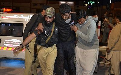 A Pakistani volunteer and a police officer rush an injured person to a hospital in Quetta, Pakistan, Monday, Oct. 24, 2016, after two separate attacks in Pakistan. (AP/Arshad Butt)