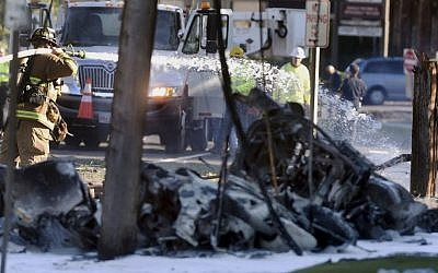 Firefighters use foam to extinguish the fire of a demolished aircraft after the plane crashed on Main Street in East Hartford, Connecticut, Tuesday, Oct. 11, 2016. (Jim Michaud/Journal Inquirer via AP)